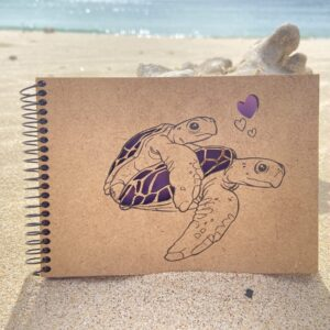 lilac notebook with turtles and hearts on the sand